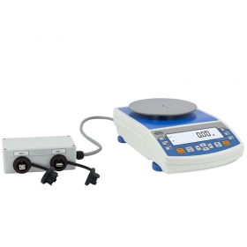 Balanza de precisión PS 1200.R2.H -   Not only do they share all the features of R series balances, but can also work in adverse operating conditions (condensed dust, drops of water falling down at different angles typical for IP 54).   These balances are equipped with innovative LCD display allowing for clear and legible presentation of a measurement result